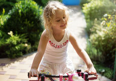 Beautiful little girl on a bicycle in the park, summer outdoor Stock Photo