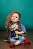 Beautiful little girl with a big bouquet of snowdrops. Stock Image