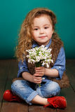 Beautiful little girl with a big bouquet of snowdrops. Royalty Free Stock Photo