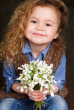 Beautiful little girl with a big bouquet of snowdrops. Royalty Free Stock Image
