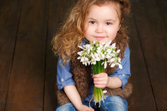 Beautiful little girl with a big bouquet of snowdrops. Stock Photo