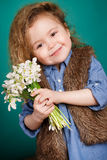 Beautiful little girl with a big bouquet of snowdrops. Royalty Free Stock Photography