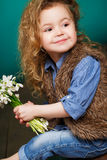Beautiful little girl with a big bouquet of snowdrops. Royalty Free Stock Photos