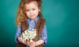 Beautiful little girl with a big bouquet of snowdrops. Royalty Free Stock Images
