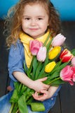 Beautiful little girl with a big bouquet of tulips. Stock Photo
