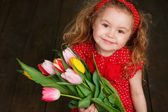 Beautiful little girl with a big bouquet of tulips. Royalty Free Stock Photography