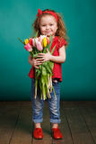 Beautiful little girl with a big bouquet of tulips. Stock Photos