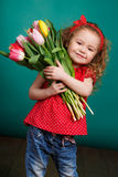 Beautiful little girl with a big bouquet of tulips. Royalty Free Stock Image