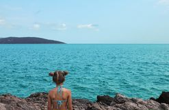 Beautiful little girl is sitting on the rocky beach Stock Photo