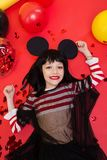Beautiful little girl in black wig posing over bright red background Royalty Free Stock Images