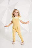 Beautiful little girl with blond hair, in yellow overalls on white background Stock Photography