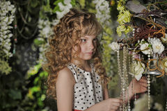 Beautiful little girl with blond locks. In the garden Stock Photo