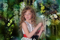 Beautiful little girl with blond locks. In the garden Stock Photos