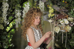 Beautiful little girl with blond locks. In the garden Stock Images