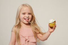 Beautiful little girl blonde with cake and candy portrait of food royalty free stock photography