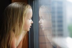 Beautiful little girl with blonde hair looking into a window at home royalty free stock image