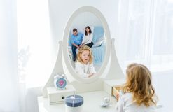Beautiful little girl with blonde long hair, looking at herself in mirror indoors. Mother and father is in reflection royalty free stock photo