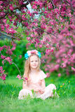 Beautiful little girl in blooming apple tree garden outdoor Stock Photography
