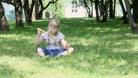 Beautiful little girl blowing soap bubbles in the garden stock video