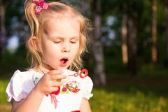 Beautiful little girl blowing soap bubbles Royalty Free Stock Image