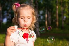 Beautiful little girl blowing soap bubbles Royalty Free Stock Photos
