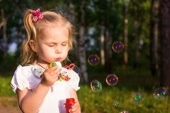 Beautiful little girl blowing soap bubbles Stock Photos