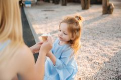 Beautiful little girl in a blue dress eating an ice cream, Mum helps and wipes her mouth stock images