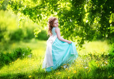Beautiful little girl in a blue dress with a large white bow in Stock Images