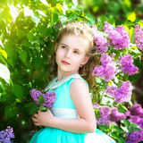 Beautiful little girl in a blue dress with a large white bow in Royalty Free Stock Images
