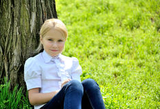 Beautiful little girl with book in the park. Beautiful young girl with book in the park, sitting on the grass near the tree and looking in the camera Royalty Free Stock Photography