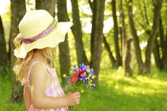 Beautiful little girl with a bouquet of flowers in nature Stock Photography