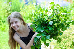 Beautiful little girl with a bouquet of green leaves Stock Photography