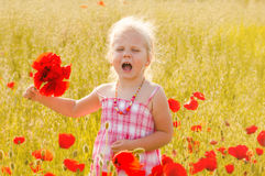 Beautiful little girl with a bouquet of red flowers stands on a stock photo