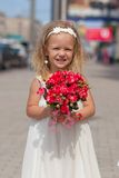 Beautiful little girl with bouquet of roses in her. Beautiful little girl with a bouquet of roses in her hand at the wedding Royalty Free Stock Photos