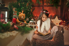 Beautiful little girl brunette read Christmas stories to her toy teddy bear. stock photography