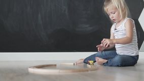 Beautiful little girl builds a wooden road for the train in the game room