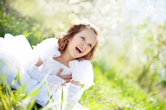 The beautiful little girl, with bush blossoming Stock Photo