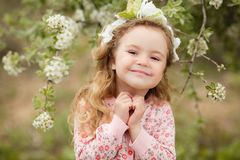 The beautiful little girl with bush blossoming tree royalty free stock images