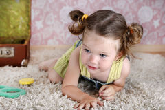 Beautiful little girl on the carpet royalty free stock photography