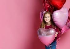Happy Little girl holding a heart-shaped ballon stock photography