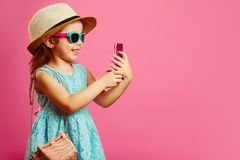 Beautiful little girl with charming smile looks at phone, has a good mood, dressed in fashionable blue dress, wearing a stock photos