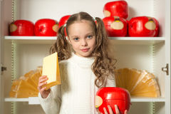 Beautiful little girl with cheese in the hands front of shelves Stock Images
