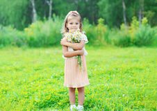 Beautiful little girl child with bouquet chamomiles flowers in summer Royalty Free Stock Photo