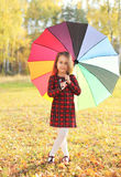 Beautiful little girl child with colorful umbrella in autumn Stock Images