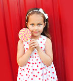 Beautiful little girl child with lollipop over red Stock Photos