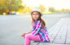 Beautiful little girl child wearing checkered pink shirt and hat in city Stock Photos