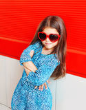 Beautiful little girl child wearing a leopard dress and red sunglasses Royalty Free Stock Photos