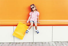 Beautiful little girl child wearing a sunglasses with shopping bags walking in city over colorful orange Royalty Free Stock Photos