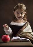 Beautiful little girl Christian, dressed in old clothes, reading the Bible, the hand gestures highlights words and main ideas Stock Image