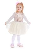 Beautiful little girl clings to her dress Royalty Free Stock Photos